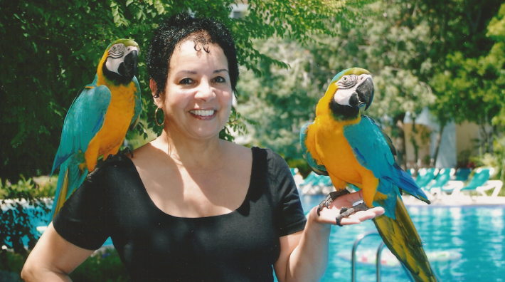 Carmen posing with a pair of toucans.